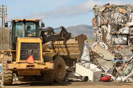 salvage yard: Wheel loader being used to pile scrap metal at a metal recycling plant