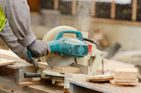 cut off saw: Worker using a electric compound cut off saw at a large commercial housing development in Oregon Stock Photo