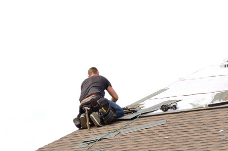 worksite: Roofer laying down asphalt roof shingles at a large commercial housing development in Oregon Stock Photo