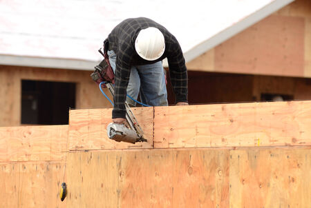 joist: Worker installing a second floor wood joist at a large commercial housing development in Oregon