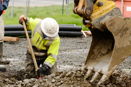 construction: Worker using a small tracked excavator to dig a hole to fix a water leak at a large commercial housing development in Oregon