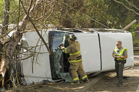 Roseburg, OR, USA - April 25, 2014: Firefighers and police at a single vehicle accident that rolled and hit a powerpole and trees resulting in minor injuries to the driver.