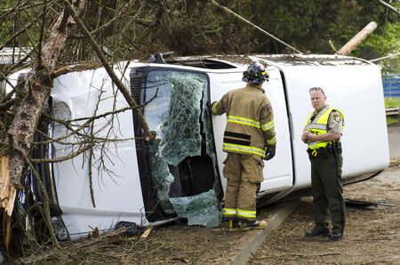 rescuing: Roseburg, OR, USA - April 25, 2014: Fire fighers and police at a single vehicle accident that rolled and hit a powerpole and trees resulting in minor injuries to the driver.