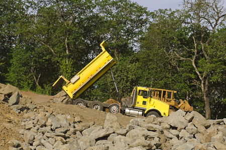 Dump truck at a new commercial construction development project dumping a load of large rock for new road