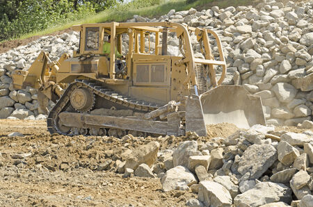 Large bulldozer moving rock and soil for fill for a new commercial development road construction project 스톡 콘텐츠