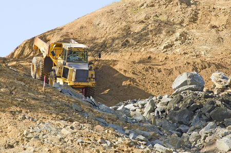 Articulated dump truck moving rock and dirt at a new commercial construction development project
