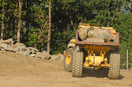 dump truck: Articulated dump truck moving rock and dirt at a new commercial construction development project