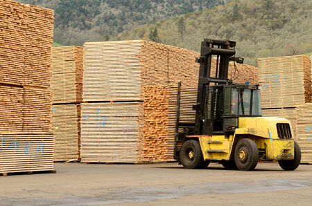 Large lift truck moving a stack of green fir 2 x 4 lumber studs at a small log processing mill in southern Oregon, ready for the drying kiln