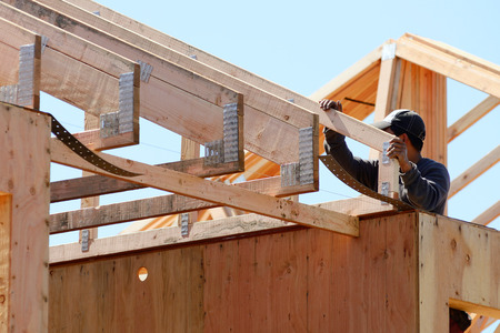 Construction framing contractor installing the roof truss system to a new commercial residential development Foto de archivo