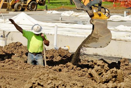 새로운 상업 주거 개발에 물 라인 트렌치를 파고 작은 트랙 괭이 굴삭기를 사용하여 건설 계약 스톡 콘텐츠