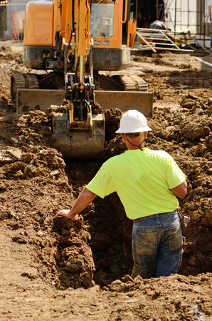 Construction contractor using a small track hoe excavator to dig a water line trench on a new commercial residential development