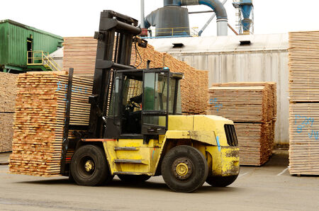 Large lift truck moving a stack of green fir 2 x 4 lumber studs at a small log processing mill in southern Oregon, ready for the drying kiln photo