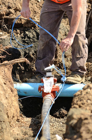 junction pipe: Excavation workers installing tracing wire on new water lines on a new commercial residential development Stock Photo