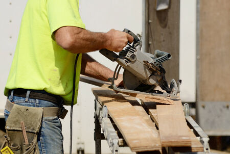 cut off saw: Framing contractor worker cutting spacer block for trim using a small circular saw on a new commercial residential development