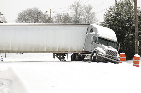 Semi truck jackknife accident into a ditch during a winter snow and freezing rain storm 写真素材