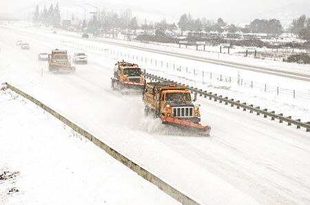 snow plow: Snow plows clearing the freeway on Interstate 5 during a winter snow and freezing rain storm