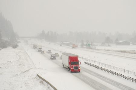 겨울 눈과 얼어 붙은 비가 오는 폭풍우 동안 고속도로 5의 세미 트럭 교통 스톡 콘텐츠