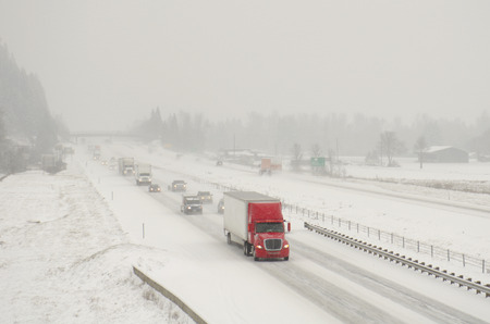winter road: Semi truck traffic on Interstate 5 during a winter snow and freezing rain storm