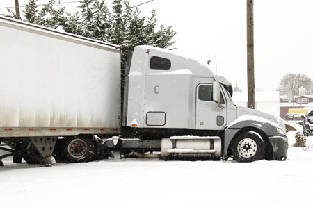 Semi truck jackknife accident into a ditch during a winter snow and freezing rain storm Stock Photo