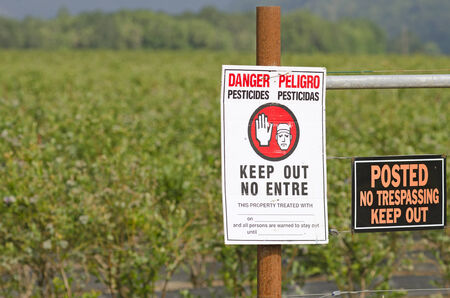 do not enter: Pesticide in use sign on a outside a field of newly treated blueberries in Oregon