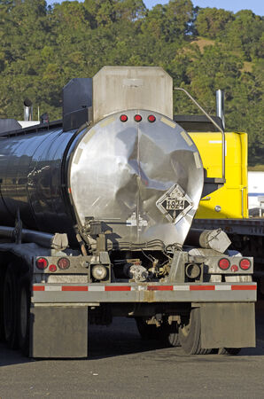 Damaged tank truck shipping sodium hydroxide, UN 1824 is parked in an industrial area Editorial