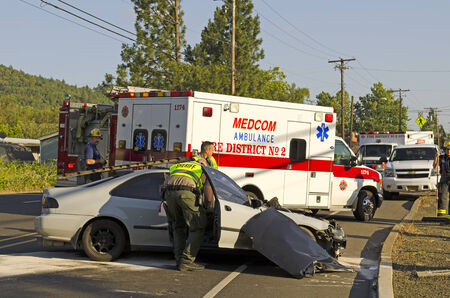 Police and fire fighters survey the scene of a single vehicle accident due to excessive speed sends the driver to the hospital in Roseburg, OR, on May 30, 2014