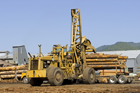 Large rubber tire log handler or loader removes a loads of cedar logs from a logging truck at a Oregon specialty wood product mill