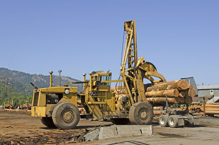 Large rubber tire log handler or loader removes a loads of cedar logs from a logging truck at a Oregon specialty wood product mill Editorial