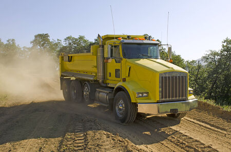 dump truck moving rock and dirt at a new commercial construction development project