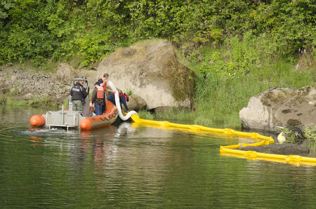 containment: Roseburg Hazardous materials team use a Douglas County Sherrif boat to deploy a floating oil containment boom on the Umpqua River following an vehicle accident where a car went into the water n Roseburg OR, USA, on June 02, 2014.