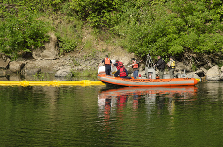 containment: Roseburg Hazardous materials team use a Douglas County Sheriff boat to deploy a floating oil containment boom on the Umpqua River following an vehicle accident where a car went into the water n Roseburg OR, USA, on June 02, 2014. Editorial