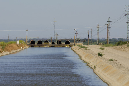 central california: Large canal of water runs through the central California valley