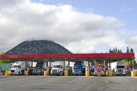 Several large over the road semi-trucks fuel up at a fueling station truck stop in California