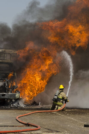 turnouts: GUSTINE, CA, USA - JUNE 18, 2014: Fire fighters respond to a semi truck and silage fire at a dairy farm in Gustine, CA, on June 18, 2014