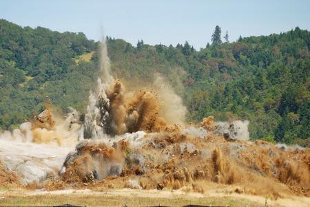 空港滑走路の拡張プロジェクトの一環として大規模な岩の丘操作をブラスト 写真素材