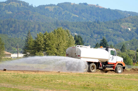 Water truck wetting down a road at the  removal  a rock hill at a airport expansion project in Oregon Reklamní fotografie