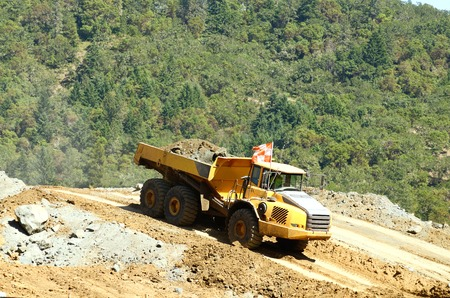 Large articulating dump tractors moving rock from a hillside blasting operation 版權商用圖片