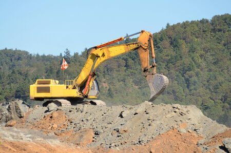 dumps: Large exchavator loading articulating dumps at an airport runway extension project