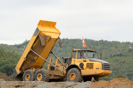 A articulated dump moving rock from a blasting site to a fill location 版權商用圖片