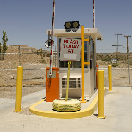 Security boot at the entrace to a mineral quarry or mine in the desert southwest with blasting sign 版權商用圖片