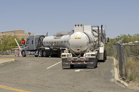 Truck and tankers with hydrochoric acid placard DOT UN 1789 enter a secure industrial facility Editorial