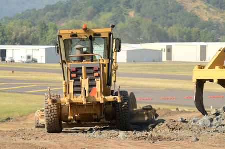 grader: Road grader smothing the road at a large construction site removing a hill during an airport runway expansion project Stock Photo