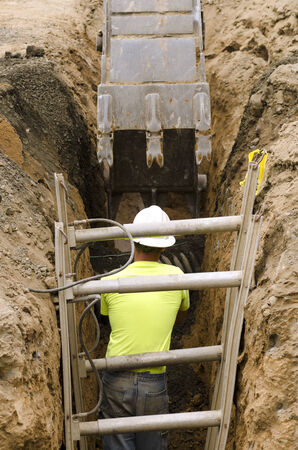struts: Construction workers using trench shoring equipment to backfill and install deep utilities at a new commercial  development