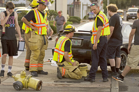knocked over: Roseburg Oregon Police and Fire department at the scene of a single car accident that knocked over a fire hydrant, July 12, 2014
