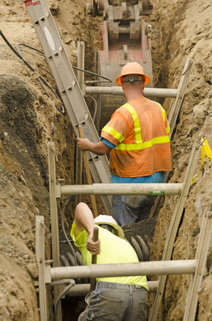 Construction workers using trench shoring equipment to backfill and install deep utilities at a new commercial  development