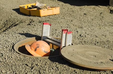 Excavation contractor entering a manhole while working on sanitary sewer system on a new commercial development