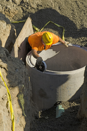 Excavation contractor installing a riser on a manhole vault on a sanitary sewer system on a new commercial development