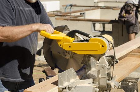 cut off saw: Framing contractor using a circular cut off  saw to trim wood studs to length.