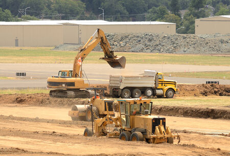 grader: equipmetn working at a construction site to extend an airport runway.