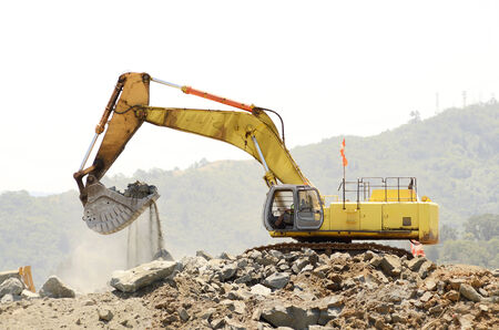 dumps: A large trackhoe or tracked excavator  moving rock from a hill at an airport runway expansion project